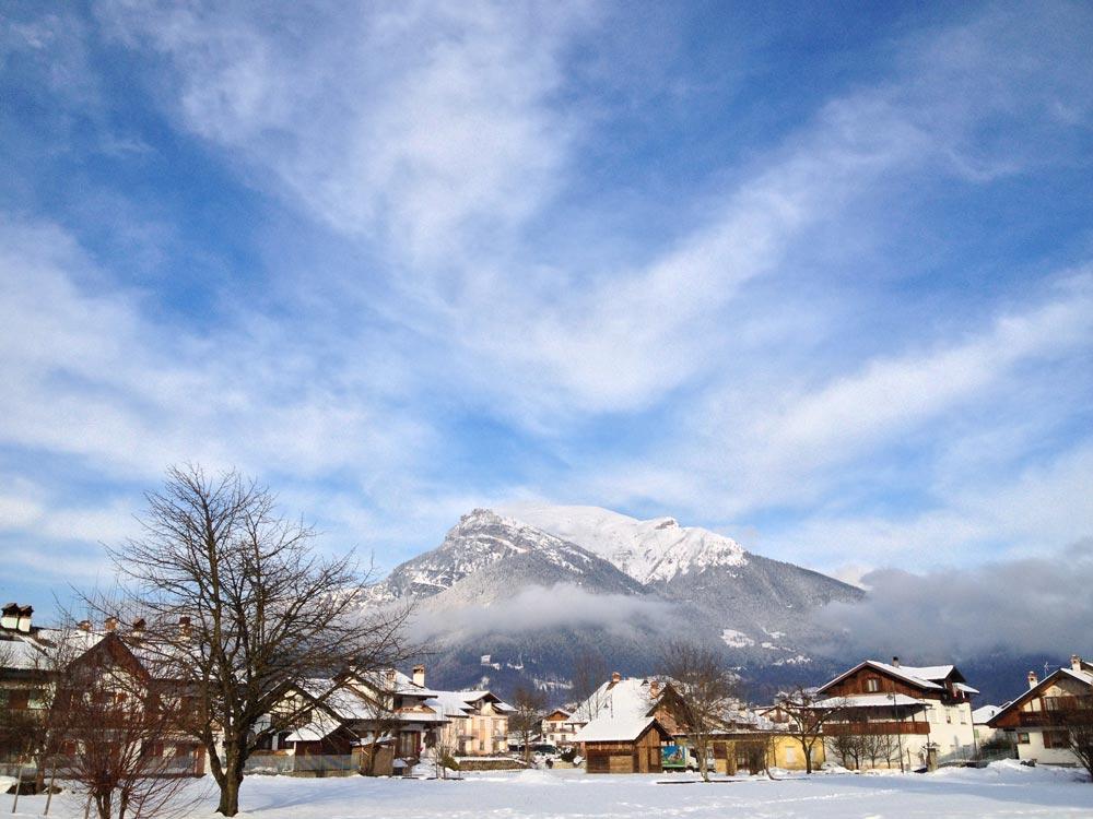 Cidade italiana (Lamon) com neve ao fundo.