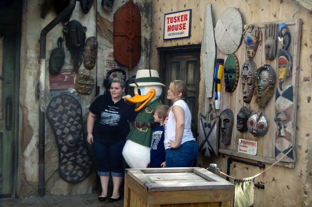 Visitantes sendo fotografados ao lado do Pato Donald