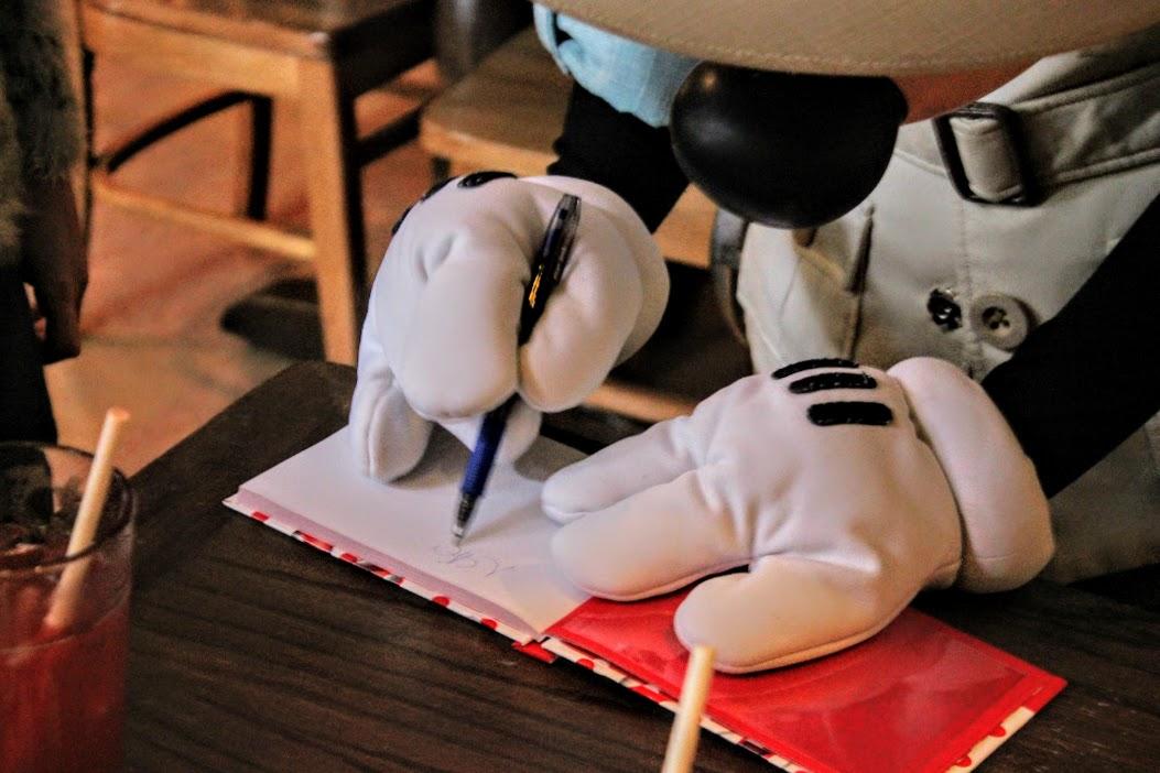 Mickey autografando caderninho no Tusker House