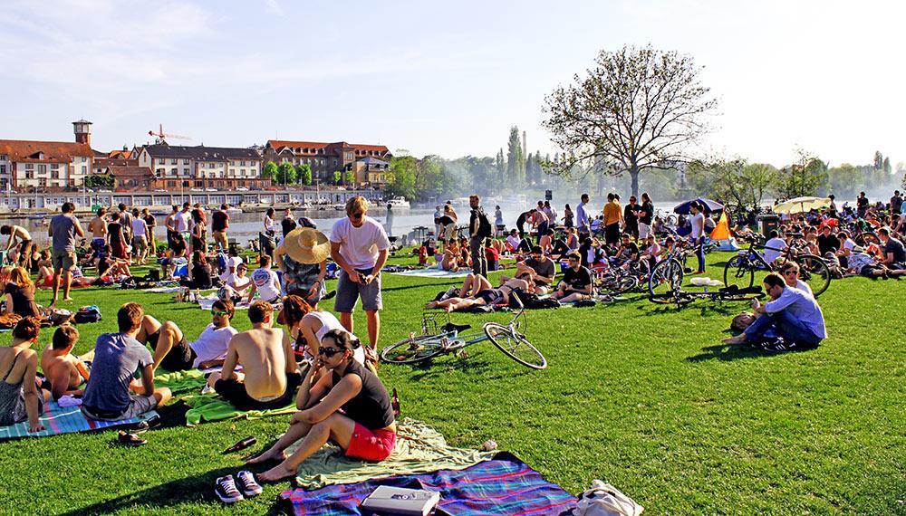 Neckarwiese, a agitada cena jovem às margens do Rio Neckar, ao fundo vê-se a fumaça do Grill Alemão