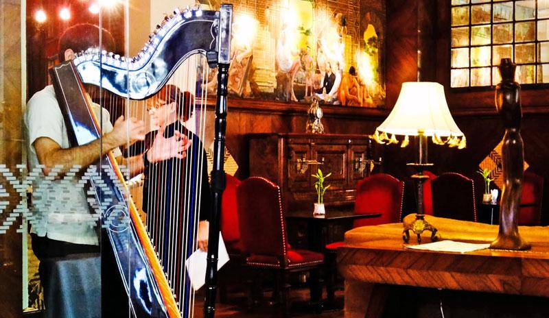 Músico tocando Harpa na entrada do restaurante