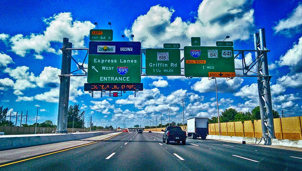 Placas indicando a entrada para a 595, rodovia com pistas que mudam o sentido ao longo do dia